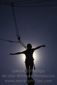 A guest at Miraval Spa in Tucson, Arizona, stands atop a telephone pole in a confinedce buildingg obstacle course.