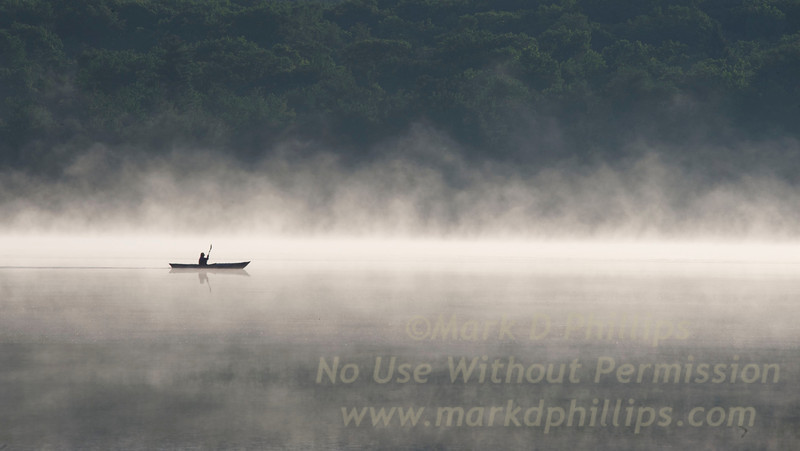 Lone Kayaker in the early morning fog on Big Pond in Otis, MA