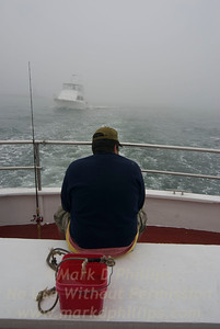 A man sits at the back of a Montauk, New York, fishing boat as they travel out in the fog on at Atlantic Ocean.