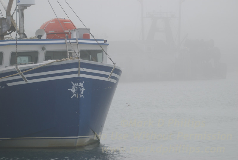 Montauk, New York, fishing boat in the fog in the harbor.