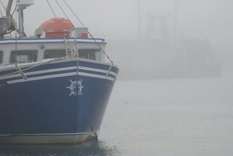 Montauk, New York, fishing boat in the fog in the harbor.
