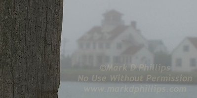 Montauk, New York, Coast Guard Station sits in the fog across the channell from a weather worn dock piling.