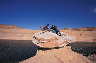 Two friends play chess atop a rock formation at Lake Powell, Utah.