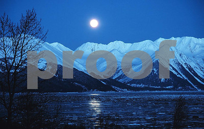 A sub-zero view of the full moon rising over Turnagain Arm in Cook Inlet south of Anchorage, Alaska