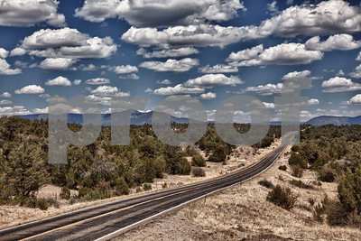 At a small rise in Highway #12 at mile post 13.5 the view of the highway with big puffy April clouds makes for an inviting trip through New Mexico.