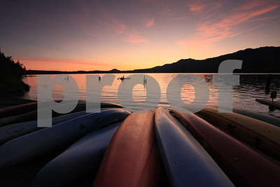 Canoes and kayaks resting on the shore of Lake Quinault in WA state show their curved lines at sunset.