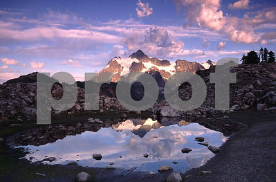 Mt. Shuksan is reflected in a small tarn near Artist Point by Mt. Baker.