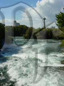 View of rapids leading to the American Falls from the pedestrian bridge to Goat Island. The Skylon Tower can be seen rising in the distance from the Canadian side of the falls. Niagara Falls, NY