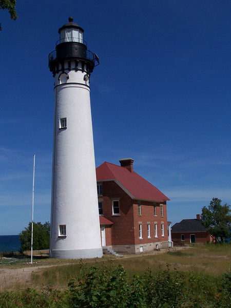 For many years sailors dreaded the eighty miles of dark shoreline that stretched east from Grand Island Lighthouse to the light on Whitefish Point. Unmarked by any navigational light, these dangerous shores claimed dozens of ships. To fill the gap, a lighthouse was placed on Au Sable Point in 1874. An eighty-seven-foot brick tower was built on a rise, placing the light about 150 feet above Lake Superior's surface.