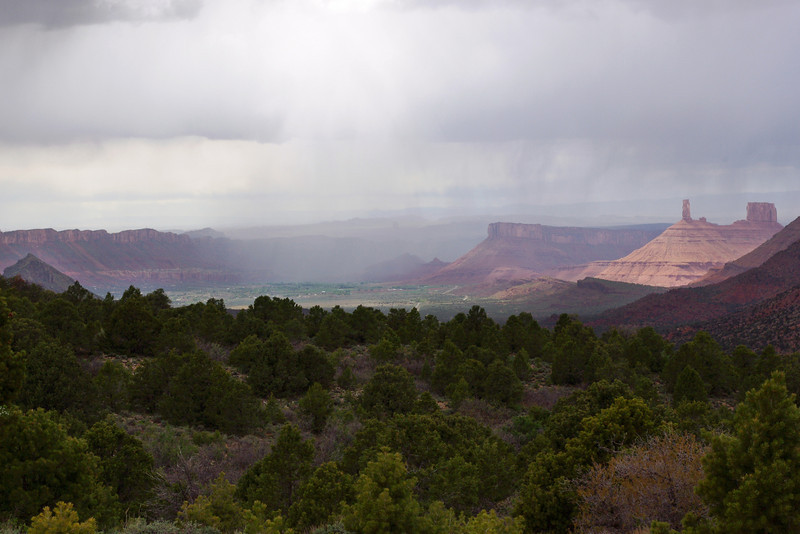 Rain showers over a desert canyon. Distant view of Castle Rock from the Castle Valley Road.