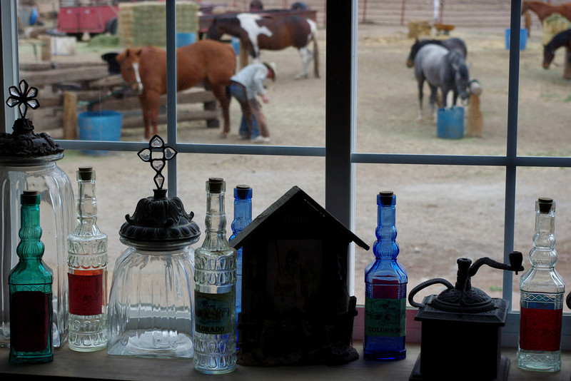 Bottles in the window of the trading post at the White Mountain Trading Post Living Museum, Fort Garland, Colorado. Note the horse being shod in the background.