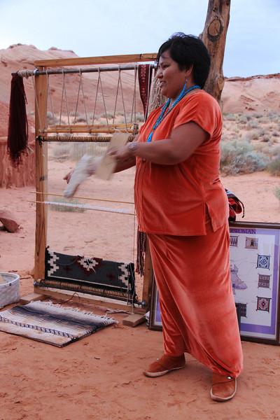 The weaver demonstrating carding.