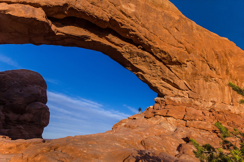 A lone visitor peers out of the North Window at Arches National Park.