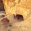Anonymous hikers passing through the hole in the hoodoo.