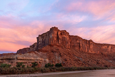 The brilliant colors of a sunrise reflecting on clouds over the top of a canyon wall with a river in the foreground