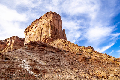 Looking up at a butte with wispy white clouds and a brilliant blue sky