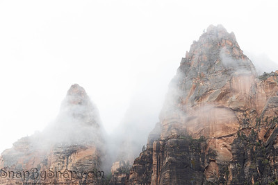 The mountain peaks of Zion National Park piercing through and overcast sky