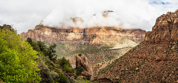 The mountains of Zion National Park in Utah with a heavy overcast and clouds dramatically passing in from of the peaks.