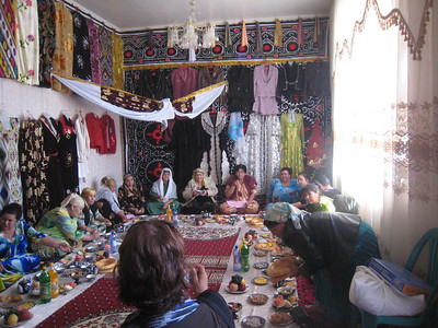 The senior female family members were seated on the floor around the edge of a room with a spread of food in front of them. The room had been cleared of any other furniture to make room for a display of the bride's dowry which included several person-high piles of blankets, floor cushions and rugs. Hanging on the walls on 3 sides of the room were the dresses the bride had been given as wedding presents, there were easily 20 or 30 including highly decorated evening gowns and a few Western style women's business suits.