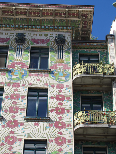 14-Majolica Haus. There is a gradation of detail and color from the bottom to the top: the green iron base, a gradual increase in complexity of the floral pattern from red to green and capped with lion heads in relief, and an elaborate overhanging eave.