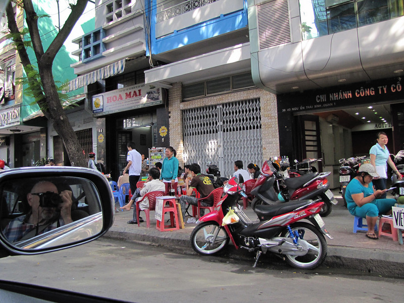 70-Sidewalks are crowded with parked motorbikes and these cafes that feature low tables and even lower stools.
