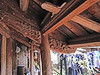 14-Carved outriggers support the overhang of a tile roof.