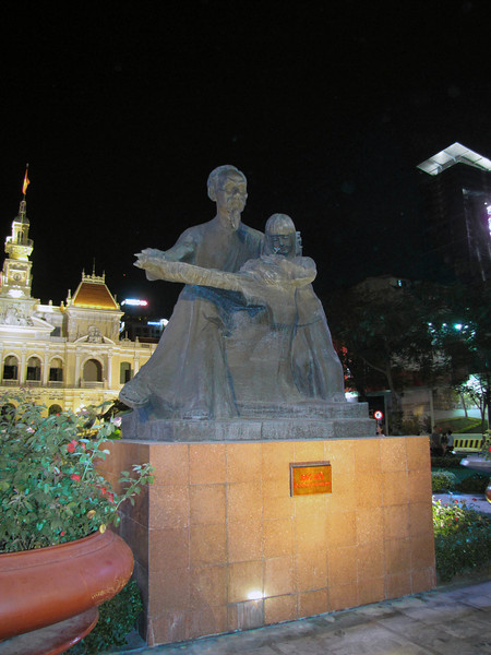 """75-Plaque reads """"Uncle Ho"""": Ho Chi Minh reading a book to a child sitting in his lap."""
