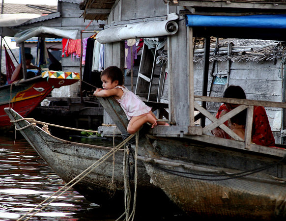 Siem Reap, Cambodia. Floating village. A child watching from her home in the floating village on the Tonle Sap Lake.