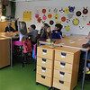 First and second graders in their (what looks to be) Ikea appointed classroom.