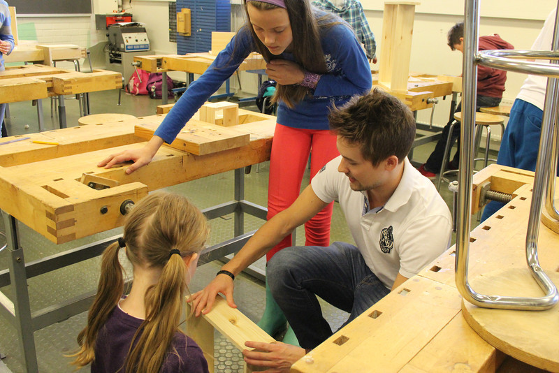 A student teacher helps students working on their woodworking project.