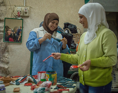 """When I took this picture, I was focused on the two women working on their crafts. What I was surprised to find was the image in the mirror of our team photographing the women. This was a """"happy accident"""" for me, and is now one of my favorites from the trip."""