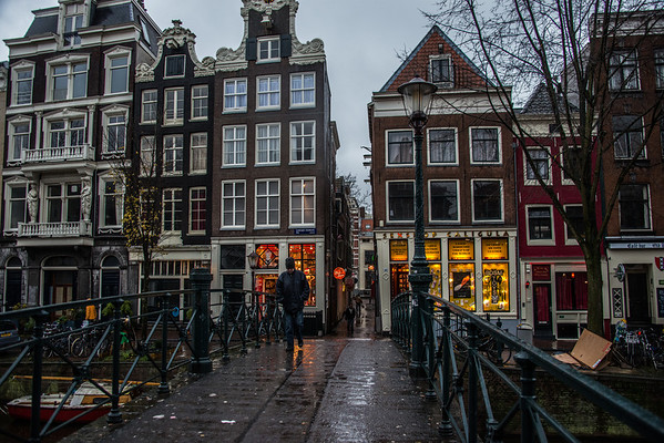 This might be my favorite picture of the trip. I love the colors in the windows of the ... uh... shops ;-) and how the bright colors contrast with the moodiness of the rest of the image from the rain and dark skies.  (I'm at the Red Light District)