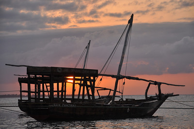 The sunset looking through one of the dhow boats in the Stone Town Harbor, Zanzibar