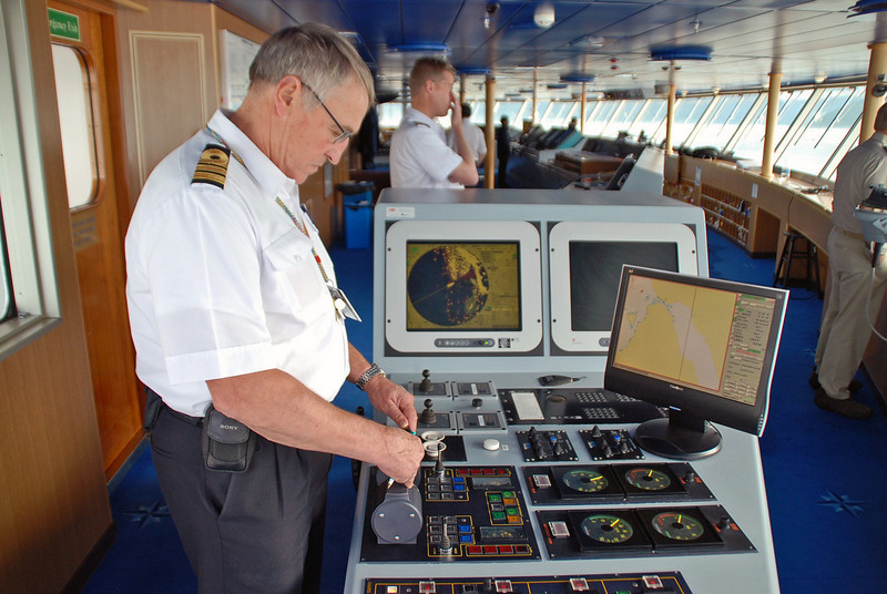 One of the ship's crew controls the ship while the Captain supervises.