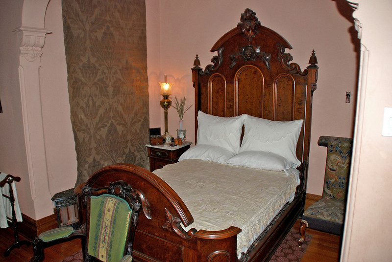 Effie's Bedroom in Craigdarroch Castle.  Effie was a daughter of Robert & Joan Dunsmuir.  A prie-dieu chair, popular in the Victorian era, is visible to the right of the bed.  The chair allowed the user to kneel on the seat and rest their arms on the back above.