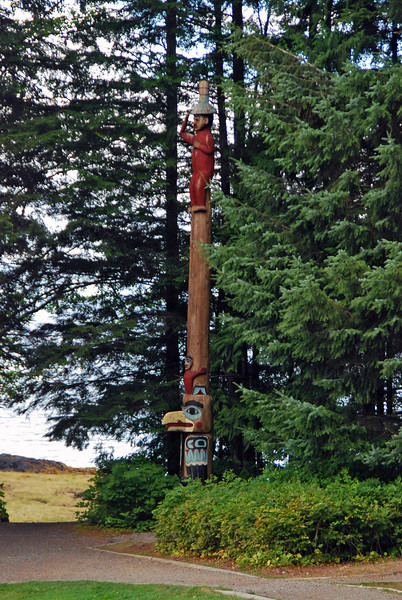 The Raven at the Head of Nass Totem Pole at Totem Bight State Historical Park.  A Tlingit pole, the chief is wearing a spruce root hat.  The bare portion of the pole indicates the high regard of the chief.