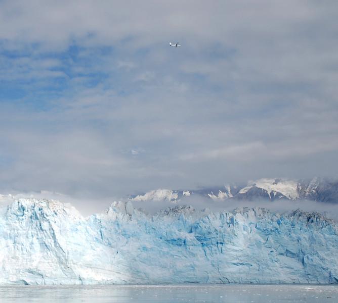 A plane flies above the glacier.