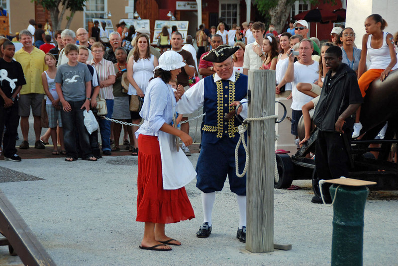 She's tied to a post in the town square with hands bound.