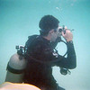 Scuba diver escort taking pictures of the helmet divers.