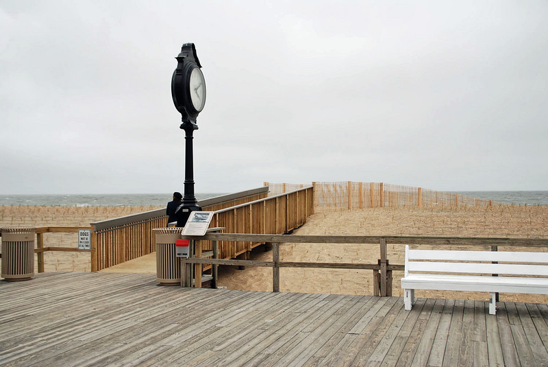 The Bethany Beach clock and a walkway over the dune towards the beach.