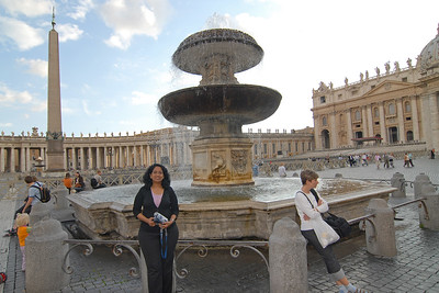 Anu at Saint Peter's Square (Piazza San Petro), is located directly in front of St. Peter's Basilica in the Vatican City which is the papal enclave within Rome. It can be reached by Via della Conciliazione and Via Paolo VI. At the center of the ellipse stands an Egyptian obelisk of red granite, 25.5 meters tall, supported on bronze lions and surmounted by the Chigi arms in bronze. There is a granite water fountain on its side.