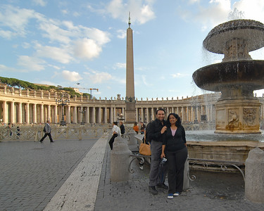 Anu and Suchit at Saint Peter's Square (Piazza San Petro), is located directly in front of St. Peter's Basilica in the Vatican City which is the papal enclave within Rome. It can be reached by Via della Conciliazione and Via Paolo VI. At the center of the ellipse stands an Egyptian obelisk of red granite, 25.5 meters tall, supported on bronze lions and surmounted by the Chigi arms in bronze. There is a granite water fountain on its side.