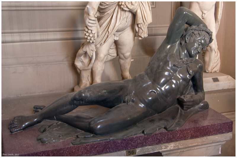 I could not find the name of this sculpture after considerable searching in several sources. It is prominently displayed in one of the central halls. I tend to think that it may be related to Bacchus, especially with the statues surrounding it.