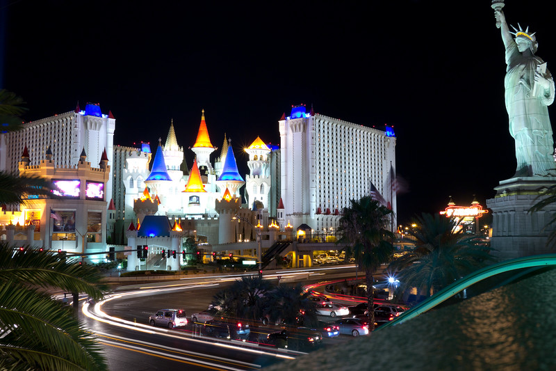 Cars whizzing by on Las Vegas Blvd and Tropicana Ave between the Statue of Liberty at New York New York and the Excalibur.