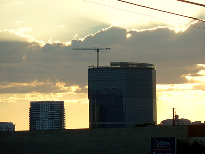 Morning sun peeking through clouds and construction.