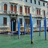 Trunks of trees brightly painted blue provide moorings for boats on water front buildings in the Grand Canal, Venice, Italy