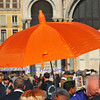 a tour guide with a bright orange umbrella shows her group around Saint Mark's Square in Venice, Italy