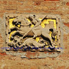 Bas relief sculpture of Saint George slaying the dragon against a background of gold mosaics in Venice, Italy