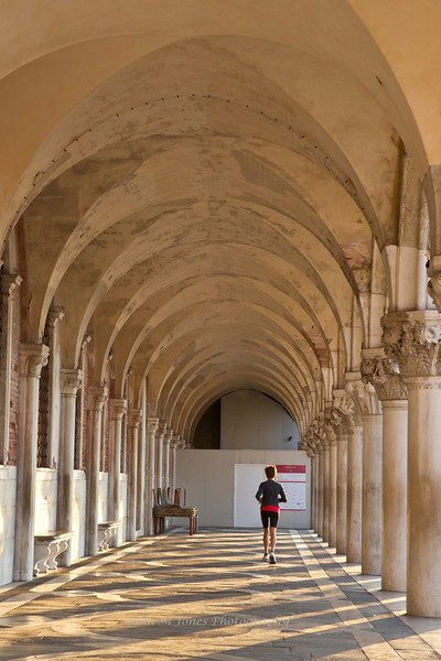 Jogger in the colonnade or loggia of Palazzo Ducale or Doge's Palace, Venice, Italy