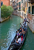 Gondolier using foot to guide gondola on small canal, Venice, Italy